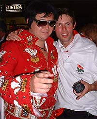 A Welsh fan dressed as Elvis jokes with an English fan
