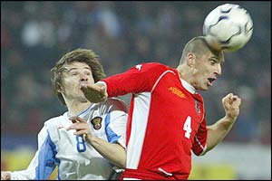 Dmitry Loskov battles for the ball with Wales' Andy Melville