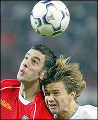 Russia's Dmitry Sichev battles for the ball with Mark Delaney