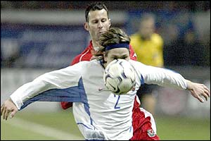 Russia's Vadim Evseev shields the ball from Ryan Giggs