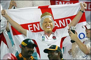 An England fan with a mask of the Queen Elizabeth on holds a flag of St George aloft