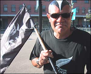 An All Black fans has his face painted and carries a New Zealand flag