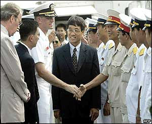 The Commander of the USS Vandegrift, Richard Rogers, is greeted by Vietnamese
