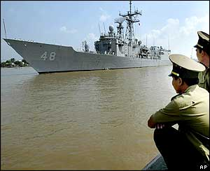Vietnamese immigration officials watch the US Navy ship Vandegrift arriving in Ho Chi Minh city
