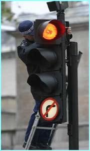 A police officer checks inside a traffic light by the building where  the President will give a speech.