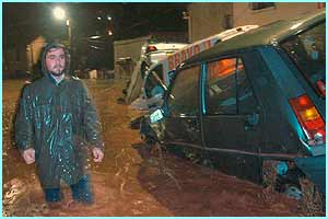A man walks past piled up cars swept away by floods.