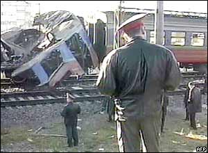 Policemen look at the wreckage of the commuter train
