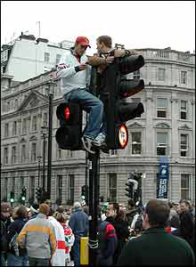 Two fans atop traffic lights next to Trafalgar Square