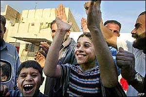 Children clap and smile in delight outside a car window in poor Sadr City suburb of Baghdad