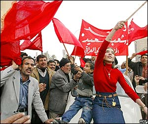 Iraqi Communist Party members chant as a young woman waves a flag in central Baghdad