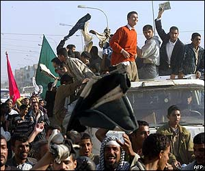 Iraqis gather in Nasiriya - some on a truck - waving flags as they celebrate the capture of Saddam Hussein