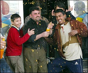 Young Iraqi men in Nasiriya laugh as they spray drink all over each other