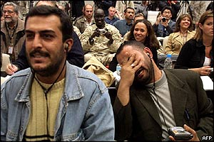 Iraqi journalist weeps and covers his face as others behind him smile at the news of Saddam Hussein's arrest