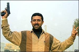 Baghdad man smiles as he waves a gun and makes a V for victory sign with his hand