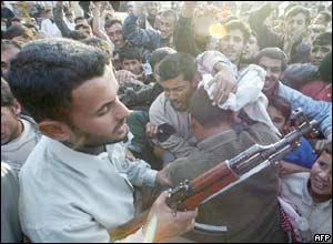 An armed Iraqi keeps discipline among crowds celebrating Saddam's capture