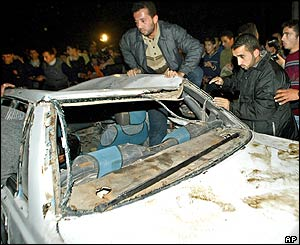 Palestinians inspect the wreckage of a car belonging to Islamic Jihad militants
