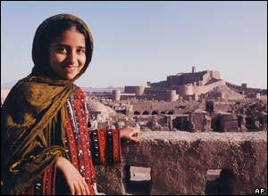 A child poses for a photo with the Bam's medieval fortress in the background