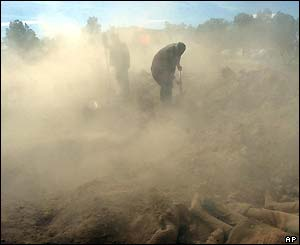 In a mass grave, Iranian relief workers pour dust on the bodies of the people who were killed in the earthquake
