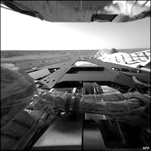 The first pictures, taken by the hazard avoidance camera on the Rover Spirit, show the rover's rear lander petal and, in the background, the Martian horizon..