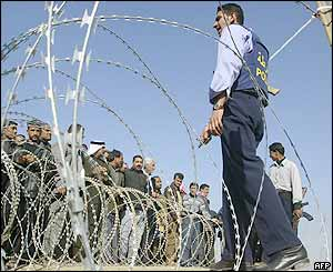 A crowd stands behind a barrier of razor wire outside Abu Ghraib prison, about 35km west of Baghdad