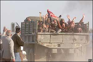 Iraqi prisoners wave from the back of a US military truck after being released from Abu Ghraib
