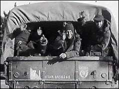 Troops waving from the back of army truck