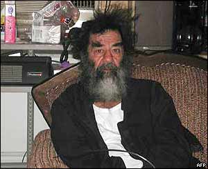 Saddam Hussein seated in an undisclosed location