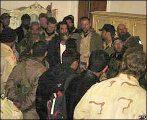 Saddam Hussein (in white t-shirt) is escorted through a crowd