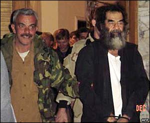 An Iraqi security guard accompanies Saddam Hussein after his capture