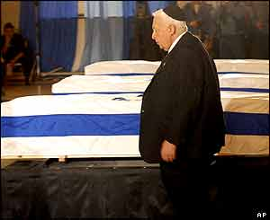 Israeli Prime Minister Ariel Sharon stands near the coffins of the three dead soldiers, Tel Aviv, 29 January 2004