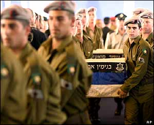 Israeli soldiers carry the coffins of three dead Israeli soldiers, returned by Hezbollah