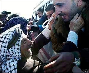 Family members (left) reach for Palestinians released from Israeli prisons, near the West Bank town of Ramallah