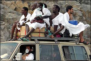 Pilgrims sit on top of a car outside Mecca