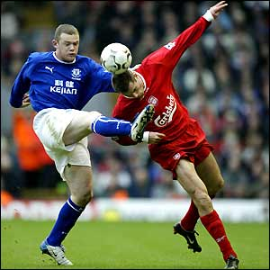 Jamie Carragher (right) gets the ball away from Wayne Rooney