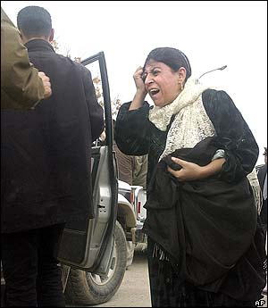 A Kurdish woman reacts while being escorted to a car outside a hospital after hearing news of the death of a relative