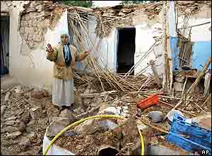 Elamrami Mimou stands in the rubble of a destroyed house in the village of Ait-Kamra