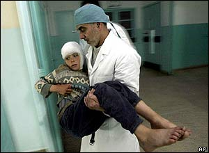 A doctor carries an injured boy