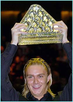 England's Paul Hunter holds up his winning trophy after he defeated England's Ronnie O'Sullivan in The Masters snooker final