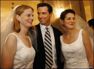 San Francisco Mayor Gavin Newsom stands between newlyweds Cissie Bonini (L) and Lora Pertle (R) during a reception at San Francisco City Hall