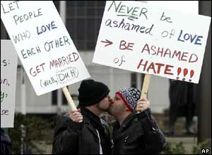 Christopher Hoffman (L) and Joshua Jacob Wiley (R) hold signs and kiss during a demonstration in favour of same-sex marriage