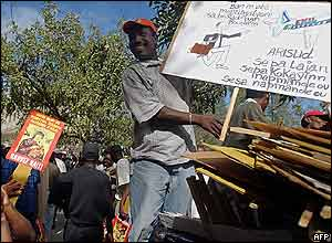 An opponent of Haitian President Aristide displays a poster showing the president attempting to flee the country