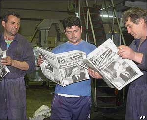 Workers in a Skopje printing shop read a newspaper's special edition