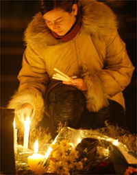 Woman lights candles in front of the parliament building during an all-night vigil.