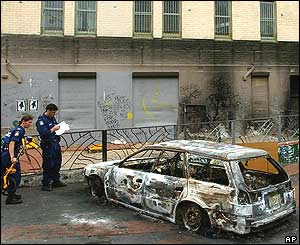 Police in Redfern inspect a burnt out car