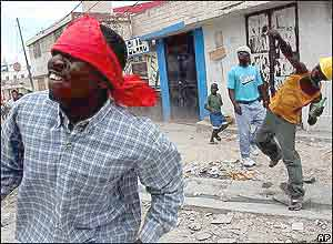 Stone-throwing demonstrators attack Aristide supporters