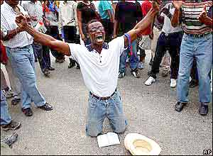 Man prays during anti-Aristide protest