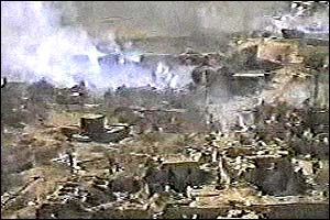 Wide shot showing smoke rising from wreckage and damaged nearby villages