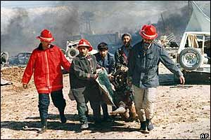 Firemen carry a victim away from the burning debris
