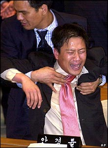 Uri MP Kim Jong-ho pulls distraught comrade Lim Jong-suck aside after the vote