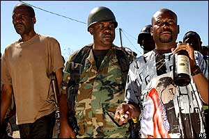 Rebel leaders Buteur Metayer (right) and Charles Blain (centre) walk in Gonaives